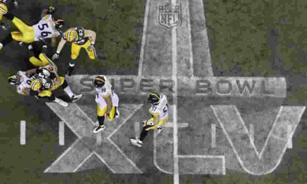 Aaron Rodgers (12), de los Packers de Green Bay, es bloqueado por Ziggy Hood, de los Pittsburgh Steelers durante la segunda mitad del partido.