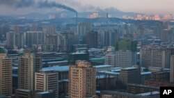 Smoke rises from factories over central Pyongyang, North Korea, Dec. 9, 2011. (AP)