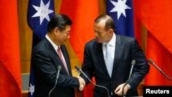 Presiden China Xi Jinping (kiri) berjabat tangan dengan Perdana Menteri Australia Tony Abbott usai upacara penandatanganan perjanjian perdagangan bebas di Parlemen Australia di Canberra (17/11).