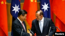 ປ. ຈີນ ທ່ານ Xi Jinping (ຊ້າຍ) ຈັບມືກັບທ່ານ Tony Abbott ຫຼັງຈາກທີ່ໄດ້ລົງນາມຂໍ້ຕົກລົງ ໃນ Canberra, ວັນທີ 17 ພະຈິກ, 2014.