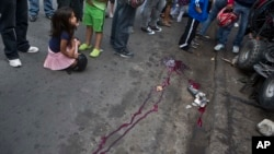 FILE - A girl closes her eyes as she sits at the scene of a murder in Tegucigalpa, Honduras, Dec. 1, 2014.