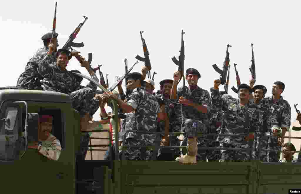 Shi'ite volunteers who joined the Iraqi army to fight the Islamic State of Iraq and the Levant gesture with their weapons in Baghdad, June 18, 2014.