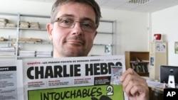 Stéphane Charbonnier aussi alias Charb, directeur de publication de l'hebdomadaire satyrique Charlie Hebdo, affiche la Une du journal, alors qu'il pose pour les photographes à Paris. (AP Photo / Michel Euler, Archives).