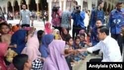 Presiden Joko Widodo berbincang dengan ibu-ibu pengungsi di tenda halaman masjid Besar At-Taqarrub Desa Keude Trienggadeng Kabupaten Pidie Jaya, 9 Desember 2016 (Foto: VOA/Andylala)