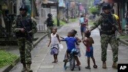 Niños juegan mientras fuerzas especiales de la Armada patrullan en Buenaventura, la principal ciudad puerto en la costa del Pacífico en Colombia.