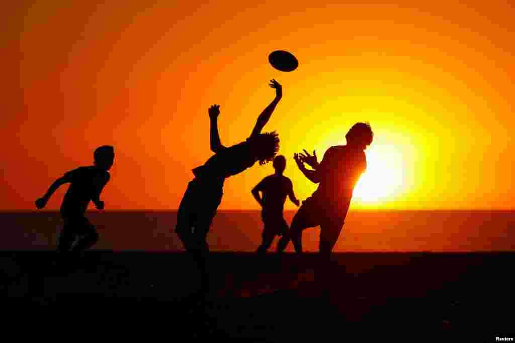 بازی کردن بر روی شن به هنگام غروب آفتاب در یکی از سواحل کالیفرنیا