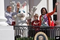 巴拉克·奥巴马总统和夫人米歇尔·奥巴马与复活节兔子在一起向参加白宫复活节彩蛋的孩子们挥手致意。(2015年4月6日)