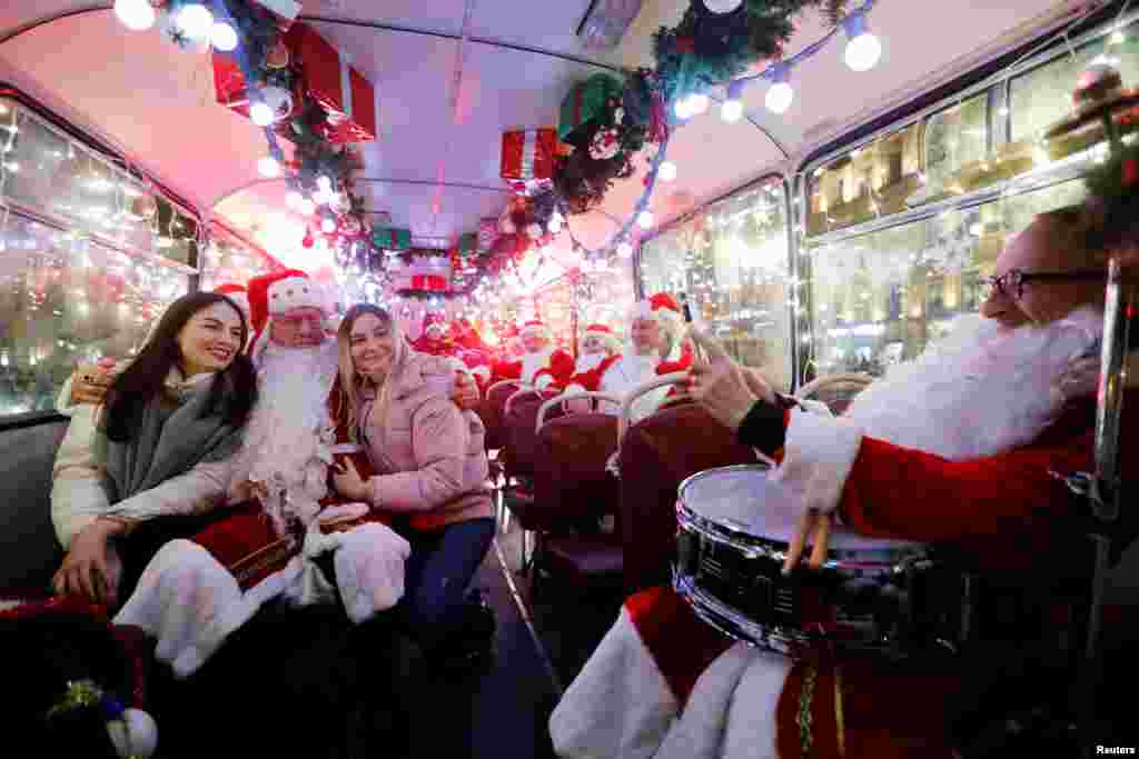 Musician dressed as Santa Claus takes a photo with passengers in a bus decorated for Christmas and New Year celebrations in central Saint-Petersburg, Russia, Dec. 24, 2019.