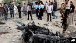 Security forces inspect the scene of a car bomb attack in Basra, 340 miles (550 kilometers) southeast of Baghdad, Iraq, Jul. 14, 2013.