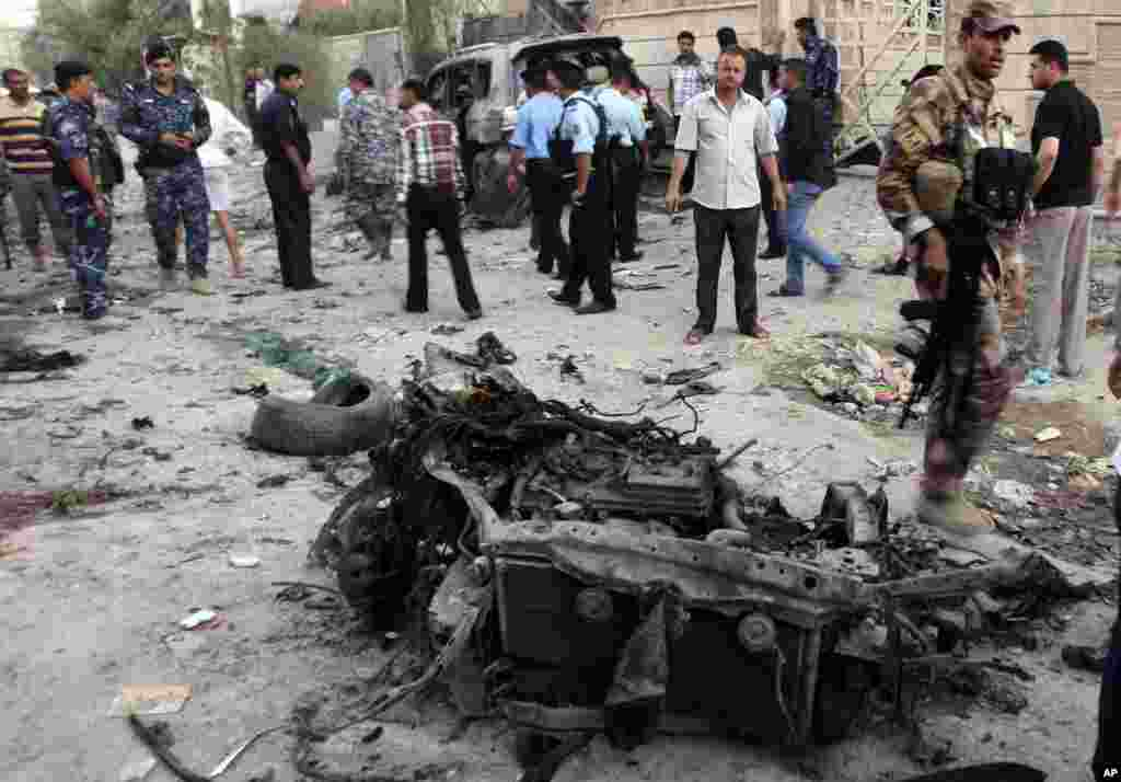 Security forces inspect the scene of a car bomb attack in Basra, Iraq, Jul. 14, 2013.