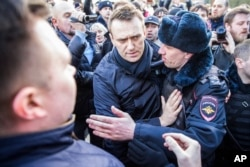 FILE - In this photo provided by Evgeny Feldman, Alexei Navalny is detained by police in downtown Moscow, Russia, March 26, 2017.
