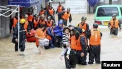 Tim penyelamat menolong penduduk setempat mengungsi ke daerah yang aman, saat hujan deras yang disebabkan oleh Topan Chan-hom, mengguyur wilayahh Shaoxing, di provinsi Zhejiang, Cina (11/7).