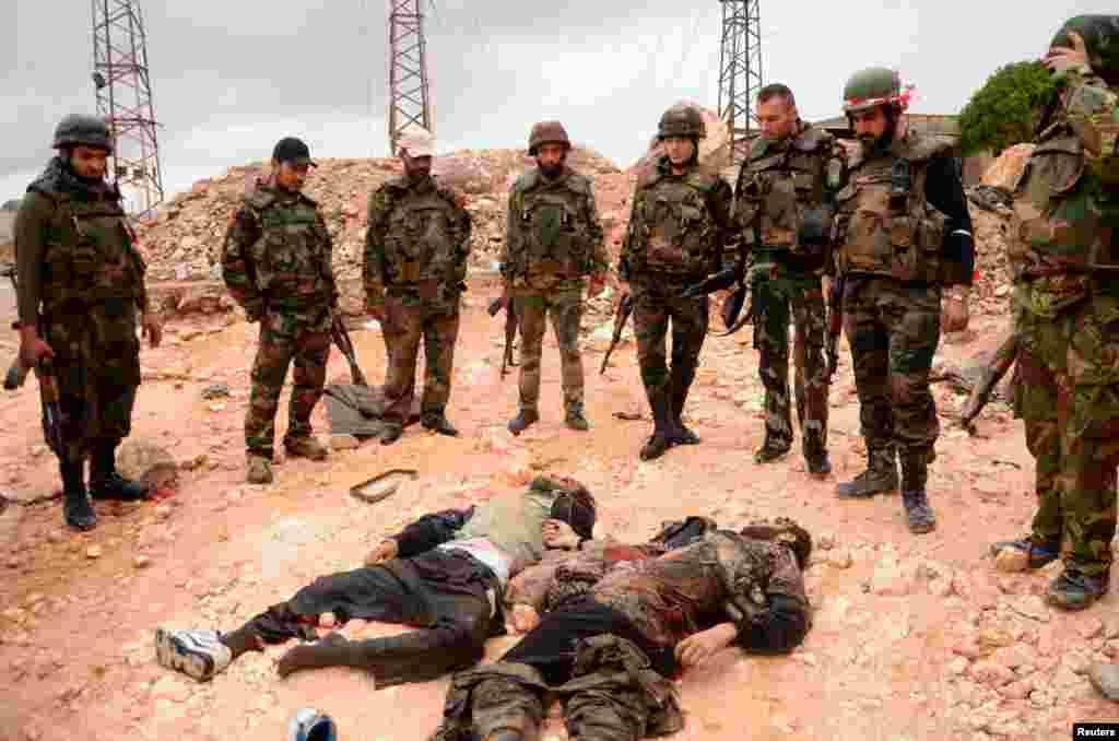 صدر بشاالاسد کے وفادار فوجی حلب میں باغیوں کی نعشوں کے قریب کھڑے ہیں۔