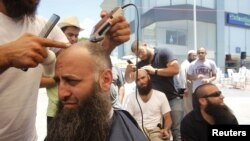 Ahmad Assir (L) and his supporters shave their heads during the sit-in in Sidon July 4, 2012.