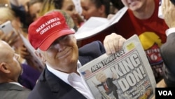 "Republican presidential candidate Donald Trump holds up the front page of the New York Post as he signs autographs in Harrington, Delaware, April 22, 2016. The Post called him ""King Don"" after his New York primary victory, but it had predicted his candida"