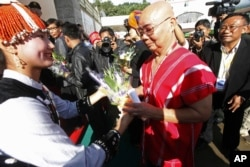FILE - General Mutu Say Poe, second from right, chairman of Karen National Union (KNU), receives flowers from a woman upon his arrival to attend ethnic armed organizations conference in Laiza, Burma, Oct. 30, 2013.