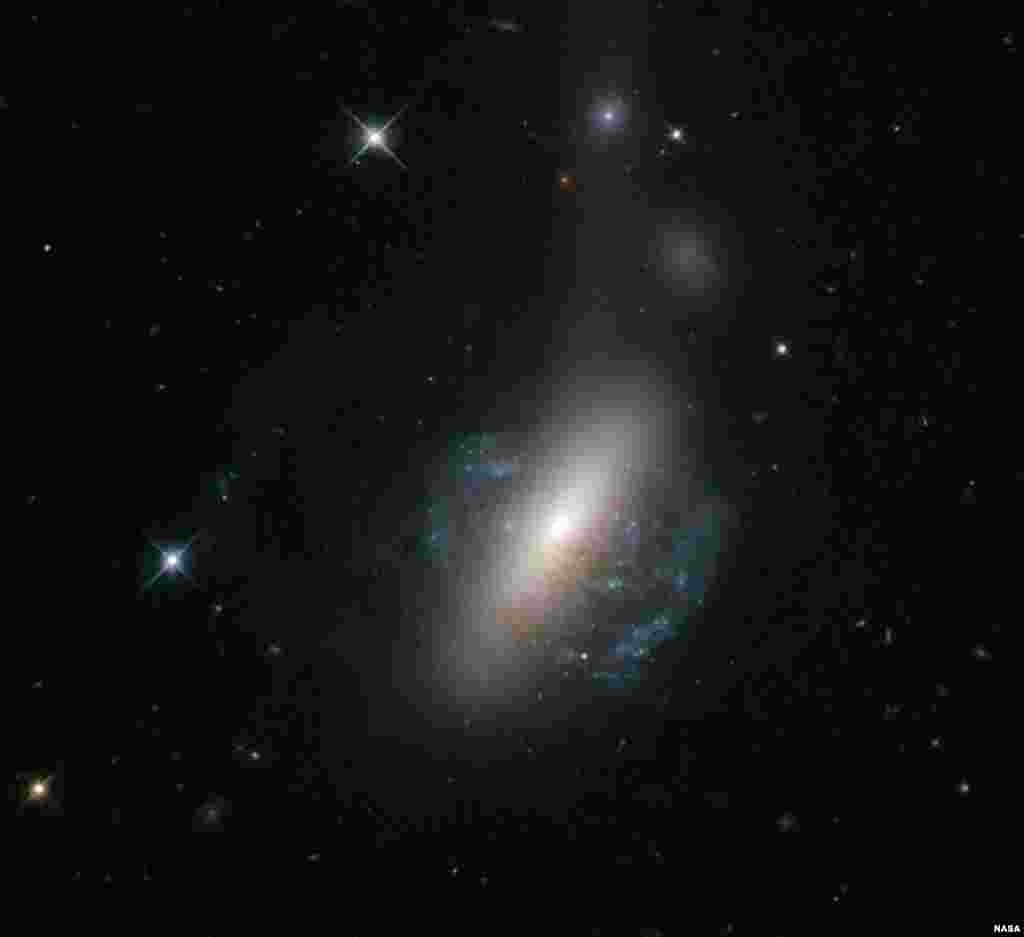 The NASA/ESA Hubble Space Telescope captures an ongoing cosmic collision between two galaxies - a spiral galaxy is in the process of colliding with a lenticular galaxy. (European Space Agency/NASA Hubble)