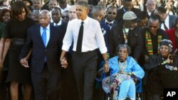 """Civil rights activist Amelia Boynton Robinson (in wheelchair, dressed in blue) holds President Barack Obama's hand, as she is being pushed across Edmund Pettus Bridge in Selma, Alabama, for the 50th anniversary of """"Bloody Sunday."""""""