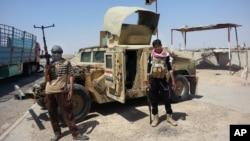 19일 이라크 북부 바이지 정유시설로 향하는 검문소를 수니파 반군들이 지키고 있다. 뒤에는 정부군으로 부터 탈취한 군용차량이 서있다.
