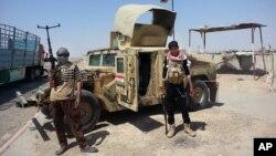 Militantes del EIIL posan frente a un vehículo militar Humvee iraquí, destruido en las afueras de la refinería de petróleo en Beiji.