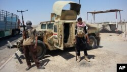 ISIL militants stand with captured Iraqi Army Humvee at a checkpoint outside Beiji refinery, north of Baghdad, Iraq, Thursday, June 19, 2014.