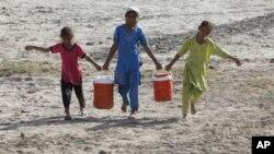 سندھ میں حالیہ سیلاب سے بے گھر ہوئئ بچیاں ایک قریبی ہینڈ پمپ سے پینے کا پانی لے جارہے ہیں۔