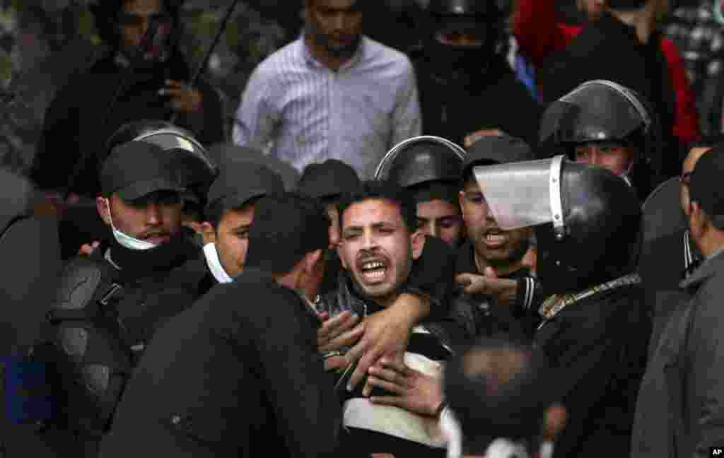 Egyptian riot police arrest a man during clashes with protesters near Tahrir Square in Cairo, Egypt, January 30, 2013.