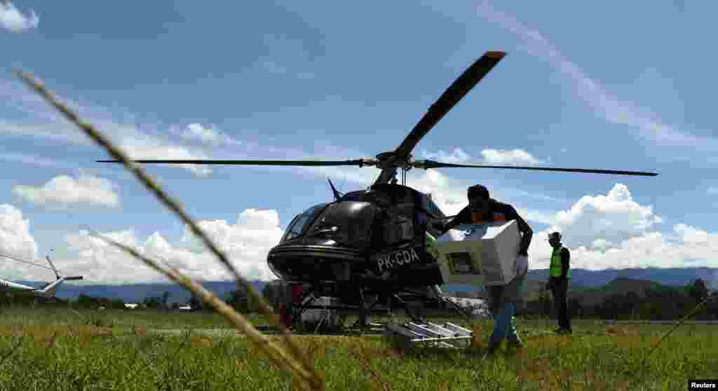 Seorang petugas membawa perlengkapan pemilu untuk dikirim dengan helikopter di Bandara Wamena, Jayawijaya, Papua, 13 April 2019. (Foto: Yusran Uccang/ Antara via Reuters)