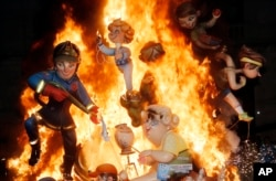"FILE - Statues burn during the traditional Fallas festival in Valencia, Spain, on March 19, 2014. Every year the city of Valencia celebrates the ancient ""Las Fallas"" fiesta,"