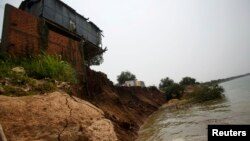 FILE - The remnants of a house built on the Mekong river banks is pictured after a portion of it collapsed when the soil underneath gave way, in Kandal province.