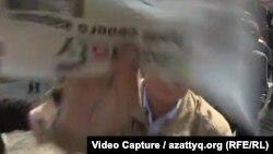 Неизвестный участник акции протеста закрывает камеру видеооператора Радио Свобода на акции в Казахстане, 22 марта 2019 года