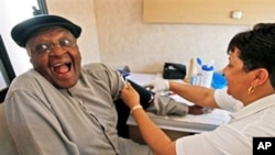 Archbishop Desmond Tutu, left, reacts as he is examined by a clinical nurse inside the 'Tutu Tester' mobile unit in Cape Town, South Africa, Thursday Oct. 22, 2009. The Tutu Tester, is a mobile unit that test people for diabetes, obesity and HIV with resu
