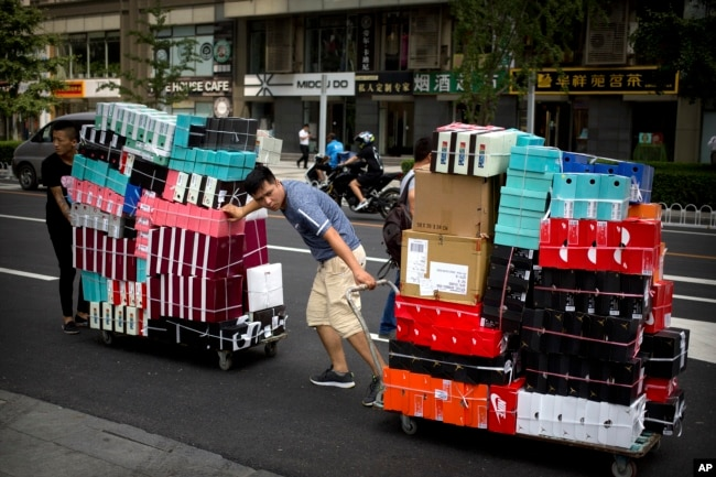 FILE - Workers pull carts loaded with shoes made by Nike and other Chinese and foreign shoe manufacturers along a street in Beijing, China, Aug. 10, 2018.