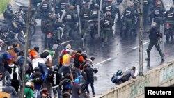 En esta foto de archivo se ve a un miembro de las fuerzas anti disturbios (derecha) apunta lo que parece ser una pistola hacia una multitud de manifestantes durante una protesta contra el gobierno del presidente venezolano, Nicolás Maduro, en Caracas, el 19 de junio de 2017.