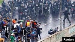 Un miembro de las fuerzas antimotines apunta con una pistola hacia los manifestantes durante una protesta antigubernamental en Caracas, el lunes 19 de junio.