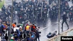Un miembro de las fuerzas de seguridad de Venezuela (derecha) apunta lo que parece ser una pistola hacia una multitud de manifestantes durante una protesta contra el gobierno del presidente Nicolás Maduro en Caracas, el 19 de junio de 2017.