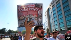 FILE - Activists, one holding a recent copy of the Cumhuriyet newspaper, march in Istanbul, July 24, 2017, protesting against a trial of journalists and staff from the newspaper, accused of aiding terror organizations.