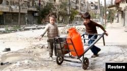 Anak-anak mendorong gerobak berisi wadah air sepanjang jalan yang hancur di kota tua Aleppo, Suriah (11/3).