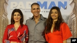 "FILE - Bollywood actor Akshay Kumar, center, with his wife Twinkle Khanna, left, and actress Radhika Apte pose for the media during the song launch of their film ""Padman"" in Mumbai, India, Dec. 20, 2017."