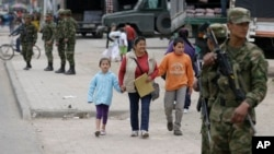 Pedestrians walk along a street guarded by soldiers in the Soacha district, southern Bogota, Colombia, Aug. 30, 2013.