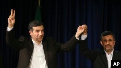 Iranian President Mahmoud Ahmadinejad, right, joins hands with his close ally Esfandiar Rahim Mashaei, as he flashes a victory sign, at the start of a press conference, May 11, 2013.
