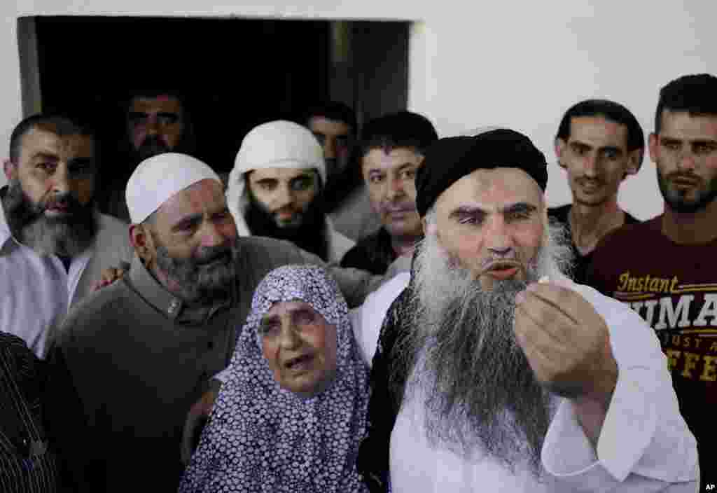 Abu Qatada stands with his mother Aisha as he speaks to the media from his parents' home in Amman, Jordan, Sept. 24, 2014.