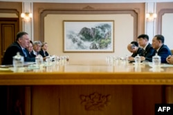 FILE - U.S. Secretary of State Mike Pompeo, left, speaks during a meeting with North Korea's director of the United Front Department, Kim Yong Chol, right, at the Park Hwa Guest House in Pyongyang, July 6, 2018.