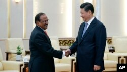 Chinese President Xi Jinping, right, shakes hands with Indian National Security Adviser Shivshankar Menon prior to a meeting at the Great Hall of the People in Beijing, Sept. 9, 2014.