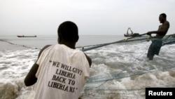 Des pêcheurs tirent leur filet hors de l'eau près de New Kru, Liberia, le 22 novembre 2005.