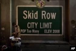 Seorang pria tunawisma mengambil makanan dari tempat sampah di daerah Skid Row Los Angeles, kota tunawisma terbesar di negara itu, 28 Oktober 2017. (Foto: AP)