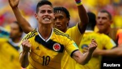 James Rodriguez (kiri) dan Juan Cuadrado dari Kolombia merayakan kemenangan atas Pantai Gading dalam Piala Dunia 2014 di Brasilia (19/6). (Reuters/Paul Hanna)