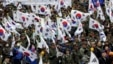 FILE - War veterans and members of conservative groups hold their national flags during a rally to call for unity between two Koreas in Seoul, South Korea, March 1, 2015.