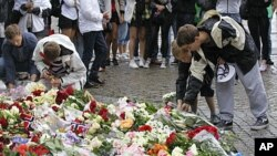 Norwegian boys place flowers on the cobble stones of the market square outside the Oslo cathedral to mourn the victims of a bomb blast in the capital and a rampage on an island in the countryside July 23, 2011