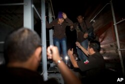 FILE - Immigration officials remove Central American migrants from a northbound freight train during a raid by federal police in San Ramon, Mexico, Aug. 29, 2014.